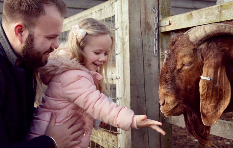 Girl and father at barleylands feeding a goat